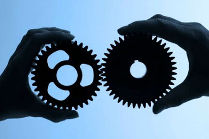 Strategic partnership, hands holding gears.